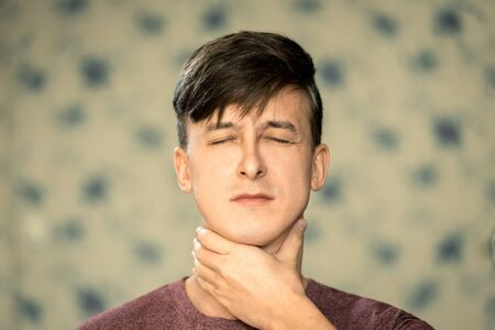 Portrait of a young man with dark hair holding on to a sore throat.