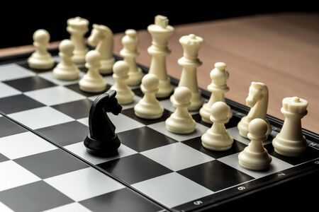 a chess black horse is standing opposite the white chess of the opponent. Symbol of leadership and confrontation.