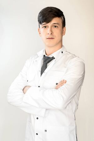 Theme of health and healthcare. A young doctor with dark hair is standing in a white coat with arms crossed, on a light background. 免版税图像
