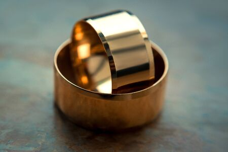 two gold wedding rings lie on the table.