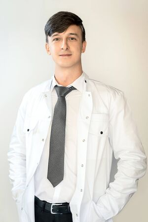 Theme of health and healthcare. A young doctor with dark hair is standing in a white coat on a light background.