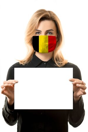 Girl with blond hair in a mask with the flag of Belgium and a blank white sheet for mockup.