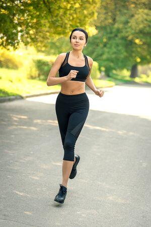 girl with dark hair in sportswear jogging. Banco de Imagens