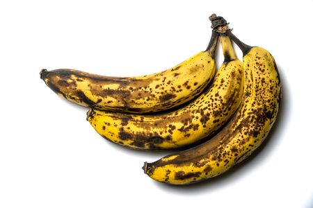 Three old banana with spots, on a white isolated background. 免版税图像