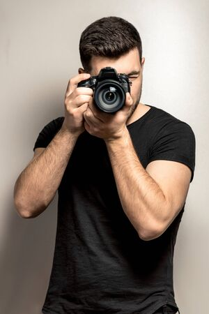 young male photographer in a black t-shirt stands with a camera on a gray background. Standard-Bild
