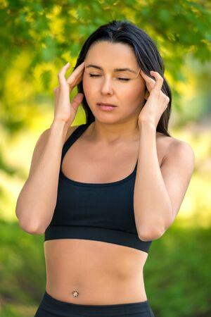 girl with dark hair in sportswear holding on to her head. Headache. 免版税图像