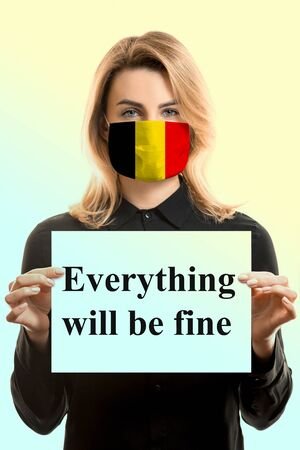 Girl with blond hair in a mask with the flag of Belgium and a sheet with the inscription