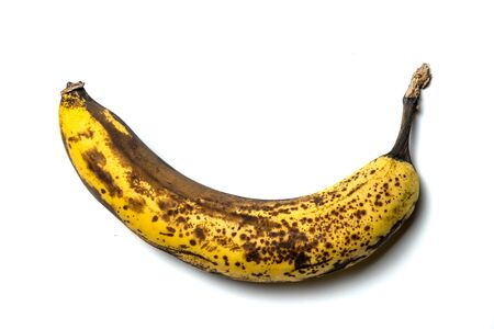 old banana with spots, on a white isolated background.