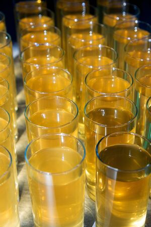 many glasses with yellow orange or lemon juice for the whole frame. 免版税图像