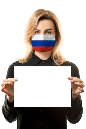 Girl with blond hair in a mask with the flag of Russia and a blank white sheet for mockup. 免版税图像 - 147716967