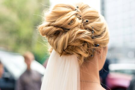 Hairstyle of the bride with blond hair, rear view. 免版税图像