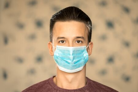 Theme of coronavirus and safety. A young man in a blue mask from a virus. 免版税图像 - 147716974
