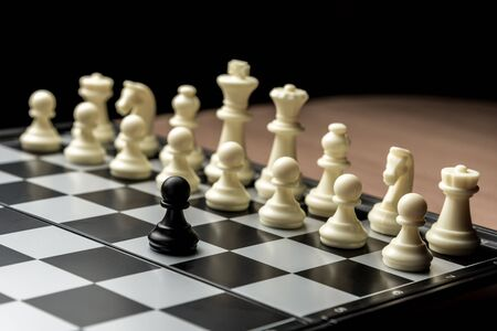 chess black pawn stands opposite white chess opponent. Symbol of leadership and confrontation. 免版税图像 - 147716975
