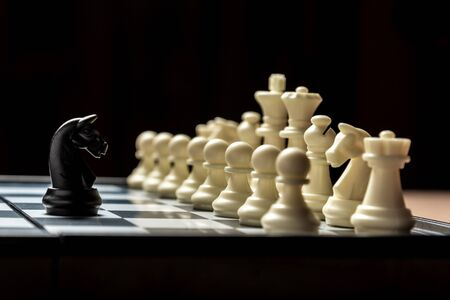 a chess black horse is standing opposite the white chess of the opponent. Symbol of leadership and confrontation. 免版税图像 - 148797839