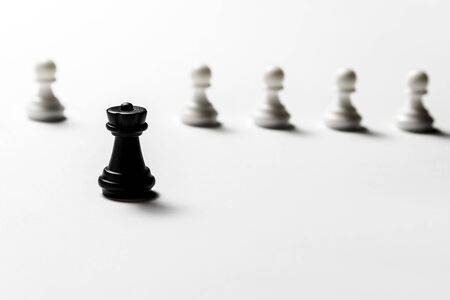 Chess black rook stands against white pawns. Symbol of leadership and confrontation.