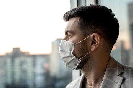 a man in a mask from viruses looks out the window, a sign of self-isolation and quarantine. 免版税图像 - 148798025