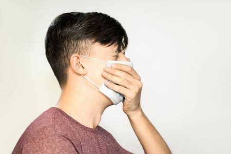 Theme of coronavirus and safety. A young man in a blue virus mask coughs into a fist.