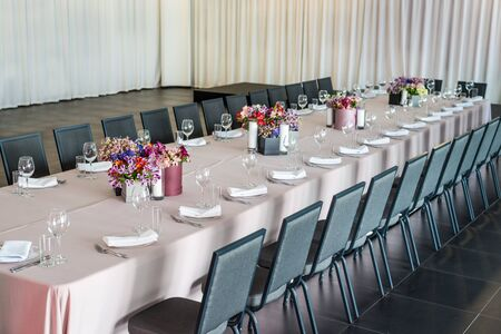a long table served with dishes and flowers.