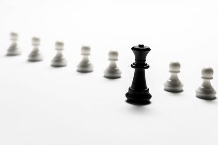 chess black queen stands against white pawns. Symbol of leadership and confrontation.