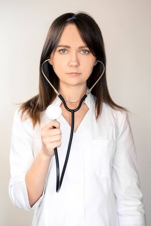 Young woman doctor with dark hair in a white medical coat, with a stethoscope, smiling.