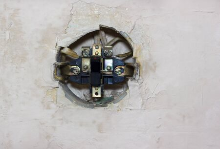 Old disassembled electric switch in the wall Stock Photo