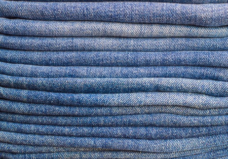 Denim fabric neatly folded. Jeans folded horizontally on each other Stock Photo