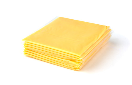Slices of processed cheese on a white background. Square slices of cheese for a burger closeup.