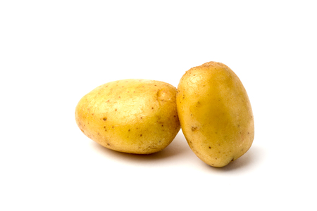 Two potatoes on a white background close-up. Two raw and washed potatoes on a white background