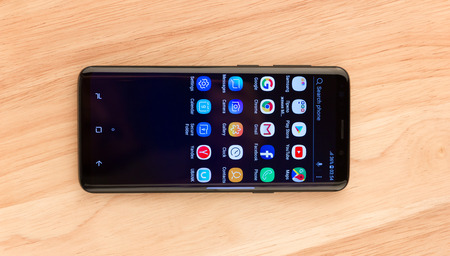 March 2018. Samsung Galaxy S9 is on the table. A new smartphone from the Samsung company lies on a wooden table close-up. On the smartphone's display are application icons.