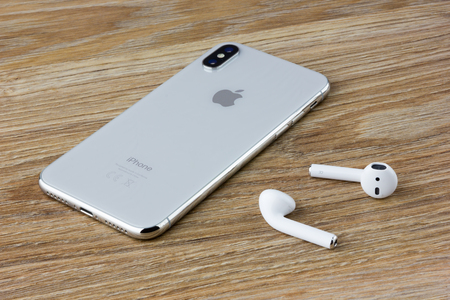 Rostov-on-Don, Russia - September 2018: The Iphone 10 lies on a wooden table next to the wireless headphones airpods from the Apple.
