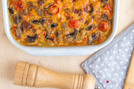 Casserole in a baking tray on a wooden table. The finished dish is baked in the oven. Foto de archivo