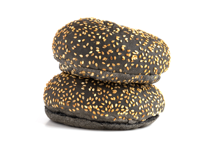 Black burger buns on a white background. Two black buns cut in half close up on a white background.