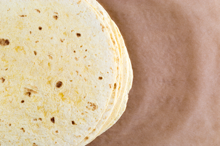 Tortilla on wrapping paper. Several mexican tortilla on the table.