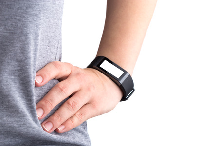 Fitness bracelet on a female hand. Hand located on the lower back close-up. Blank display.