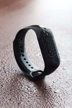 Fitness bracelet on the table. Bracelet poured with water on a wooden surface. Stok Fotoğraf