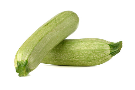 Courgettes on a white background. Green fresh zucchini close up.