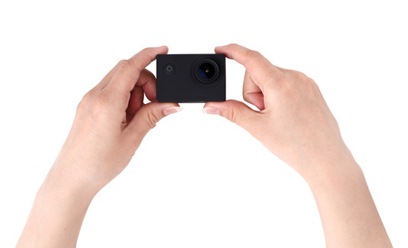 Action camera on a white background. Black portable camera closeup in hands on a white background.