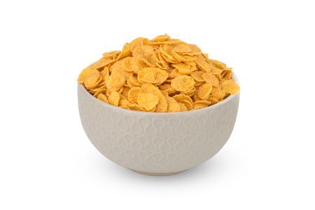 Copos de maíz sobre un fondo blanco. Copos de maíz en un tazón de fuente de cerca.
