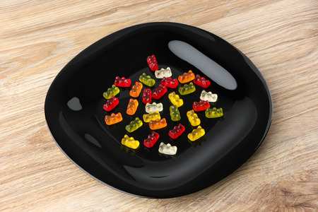 Jelly bears on a black plate. Multicolored sweets in a plate on a wooden table.