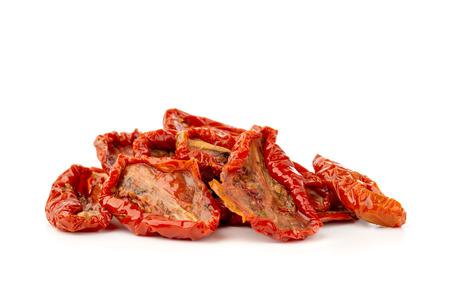 Tomates secos sobre un fondo blanco. Cerca de rodajas de tomates secos en aceite. Foto de archivo