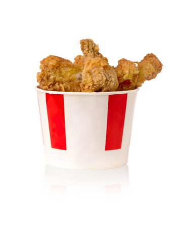 Fried legs and wings on a white background. Chicken wings and legs deep-fried in a cardboard bucket. Imagens