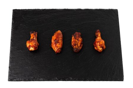 Fried wings close-up. Buffalo wings on a stone slate board isolated on white. Top view.