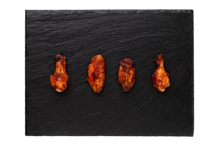 Fried wings close-up. Buffalo wings on a stone slate board isolated on white. Top view. Stockfoto - 130015987
