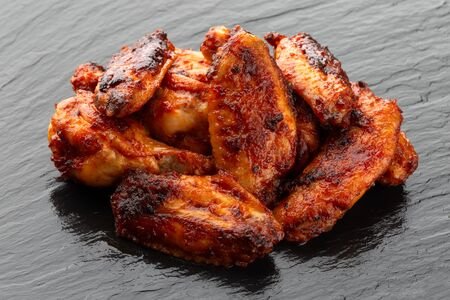 Fried wings close-up. Buffalo wings on a slate surface. Stockfoto - 130015990