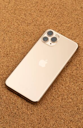 Apple iPhone 11 Pro on cork surface. Apples new smartphone close-up. Smartphone and box from it on a white background.
