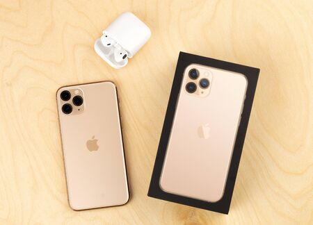 Rostov-on-Don, Russia - october 2019. Apple iPhone 11 Pro on a wooden surface. Apples new smartphone close-up. Smartphone and AirPods earphones and a box from it. Redactioneel