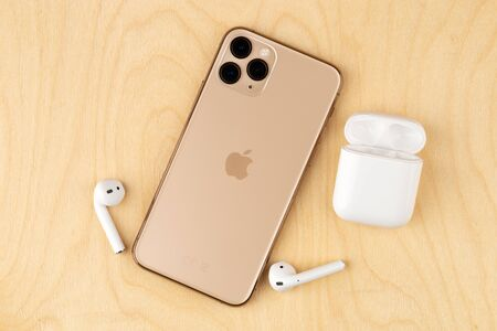 Rostov-on-Don, Russia - october 2019. Apple iPhone 11 Pro on a wooden surface. Apples new smartphone close-up. Smartphone and AirPods earphones. Redactioneel