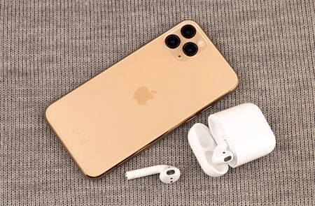 Rostov-on-Don, Russia - october 2019. Apple iPhone 11 Pro on gray knitted fabric. New smartphone from the company Apple close-up. Smartphone and AirPods earphones.