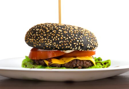 Black burger on a white plate. Beef patty burger, cheddar cheese, lettuce, bacon, tomato and balsamic sauce. The bun is made with the addition of ink cuttlefish.
