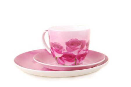 Pink cup and saucer decorated with colours on a white background photo